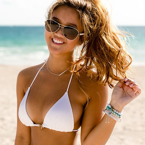 young woman in white bikini top and shades by the beach